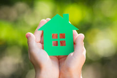 Paper house in hands. Child holding paper house in hands against spring green background Stock Photos