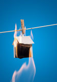 Paper house on fire. A paper house hanging from a clothes line on fire Stock Photo