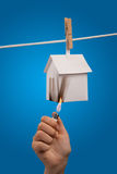 Setting a house on fire. A paper house hanging from a washing line by a clothes peg with a hand holding a lighter setting it on fire with a blue sky background Stock Image