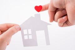 Paper house and heart shape. Paper house and  heart shape in hand on a white background Royalty Free Stock Photography