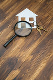 Paper house and key with Magnifying Glass, House hunting Stock Images