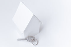 Paper house and key on white, copy space background. Stock Images