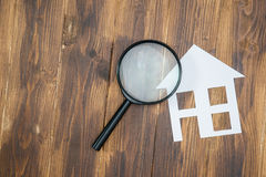 Paper house with Magnifying Glass, House hunting Royalty Free Stock Images