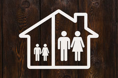 Paper house with man, woman and children inside. Family concept Royalty Free Stock Photos