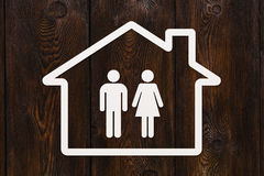 Paper house with man and woman inside. Housing, family concept Stock Photo