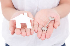 Paper house and metal key in female hands Royalty Free Stock Images