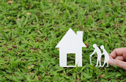 Paper house and old people on the grass Royalty Free Stock Photo