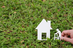 Paper house and old people on the grass Royalty Free Stock Images