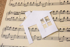 Paper house on a paper with musical notes Royalty Free Stock Image