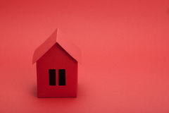 Paper house. Red paper house on red background Royalty Free Stock Images