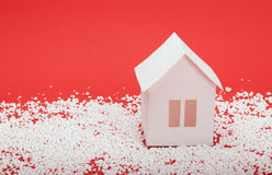 Paper house in snow on red background Royalty Free Stock Photos