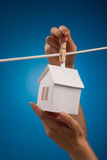 Real estate concept. Paper houses with clothespins, hanging from rope on blue background Stock Image