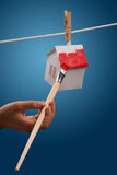 Home Renovation - real estate concept. Paper houses with clothespins, hanging from rope on blue background Stock Photography