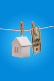 Real estate concept. Paper houses with clothespins, hanging from rope on blue background Stock Photography