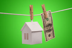 Real estate concept. Paper houses with clothespins, hanging from rope on green background Royalty Free Stock Photos