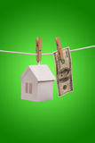 Real estate concept. Paper houses with clothespins, hanging from rope on green background Stock Photos