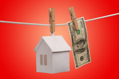 Real estate concept. Paper houses with clothespins, hanging from rope on red background Royalty Free Stock Photography