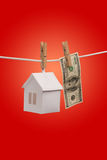 Real estate concept. Paper houses with clothespins, hanging from rope on red background Stock Photos