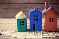 Paper houses stands over a wooden background Royalty Free Stock Photos