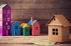 Paper houses stands over a wooden background Stock Photo