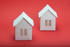 Paper houses. White paper houses on red background Stock Photo