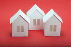 Paper houses. White paper houses on red background Royalty Free Stock Photos