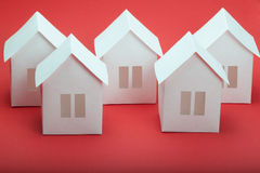 Paper houses. White paper houses on red background Royalty Free Stock Photography