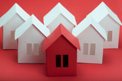 Paper houses. White and red paper houses on red background Stock Photos