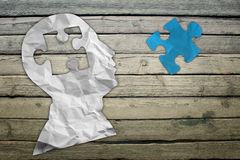 Paper humans head with blue puzzle symbol Stock Photography