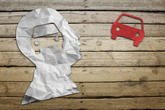 Paper humans head with car symbol. On wood deck background Stock Photos