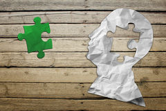 Paper humans head with green puzzle symbol Stock Images