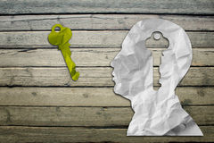 Paper humans head with key sign. Paper humans head with question symbol on wood deck background Royalty Free Stock Photos