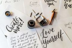 Paper, ink, calligraphy pens and inscriptions. Lettering workshop details. Inscribing ornamental decorated letters. Calligraphy, graphic design, lettering royalty free stock photography