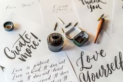 Paper, ink, calligraphy pens and inscriptions. Lettering workshop details. Inscribing ornamental decorated letters. Calligraphy, graphic design, lettering royalty free stock photos