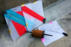 Paper Kites and thread. Colorful paper kites lying on the floor with a bundle of thread Royalty Free Stock Photos