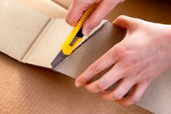 Paper knife in person hands cutting cardboard piece. Cardboard background. Close-up royalty free stock photography