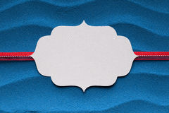 Paper label and red ribbon on blue background Stock Photography