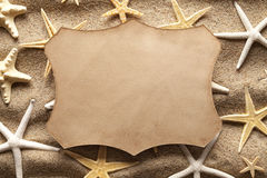Paper label and starfishes on sand Stock Images