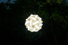 Paper lantern with awesome swirl effect against a black foliage backdrop Stock Photography