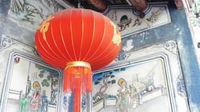 Paper lanterns on shabby building with blue traditional paintings. Red paper lanterns hanging on ceiling of weathered. Concrete temple building on sunny day in stock video footage