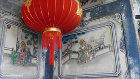Paper lanterns on shabby building with blue traditional paintings. Red paper lanterns hanging on ceiling of weathered. Concrete temple building on sunny day in stock video