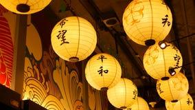 Paper lanterns shining on street. Beautiful paper lanterns shining while hanging in narrow passage on Japanese street stock video