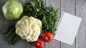 Paper leaf and composition of vegetables on grey wooden desk. Royalty Free Stock Image