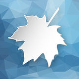 Paper leaf over geometric background. Paper 3d maple leaf over blue abstract geometric triangular background Royalty Free Stock Photo