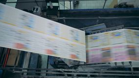 Newspaper on a working conveyor, top view. Paper on a line at a print office stock video