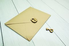 A paper mail envelope is closed with a lock next to the key on a white table, a secret royalty free stock photo