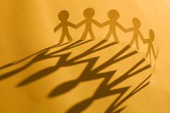 Paper man chain. Holding hands on orange. Symbol of unity, brotherhood and teamwork Royalty Free Stock Image