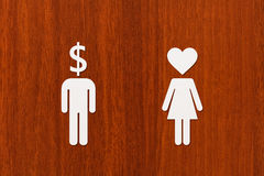 Paper man dollar head and woman with heart. Love vs money concept Royalty Free Stock Images