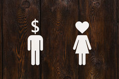 Paper man dollar head and woman with heart. Love vs money concept Stock Images