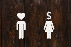 Paper man heart head and woman with dollar. Love vs money concept Royalty Free Stock Photos